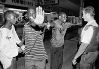 Policeman confronting three men, Johannesburg, South Africa