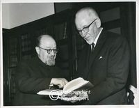 "Professor Israel Abrahams, with the Speaker of the House of Assembly, Mr. Klopper, reads passages from a copy of Professor U. Cassuto's book ""From Noah to Abraham"", Cape Town"