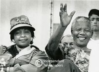 Nelson Mandela sits next to his wife and waves to supporters, Cape Town