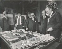 Men look at architect's model of houses to be constructed in Mitchell's Plain, Cape Town