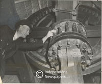 Man inspects wooden cogs at Mowbray Mill, Cape Town