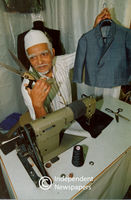 Tailor shows clothing that he has made, Cape Town