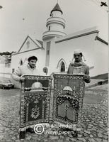 Two men hold their prayer rugs in front of Mosque, Cape Town