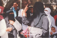 Woman wearing burqa gestures while talking to companion, Cape Town