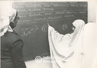 Young girl writes on blackboard while teacher watches, Cape Town