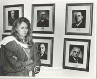 Woman stands in front of photos of previous N.P. leaders, Cape Town