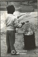 Boy warms his hands near a burn barrel, Cape Town