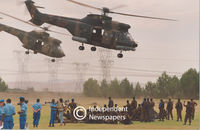 Two army helicopters lift off carrying soldiers, while other watch, Cape Town