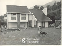 Woman with her dog in front of her house, Cape Town
