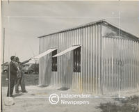 Men inspect aluminium house, Cape Town