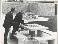 Two men stand at a park chess table, Cape Town
