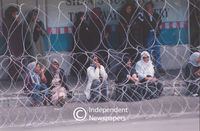 Women sit on pavement behind barbed wire fence, Cape Town