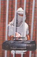 Man wearing balaclava holds a radio between bars, Cape Town