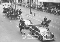 Officers mounted on horses escort cars down the road, Cape Town