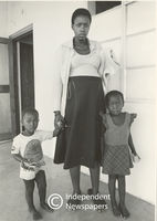 Pregnant woman stand holding her two kids hands, Cape Town