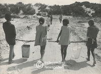 Children carry buckets of water hanging from sticks, Cape Town