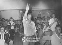 Man gestures the peace sign in a crowded hall, Cape Town