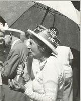 Female supporter stands wearing a hat while holding an umbrella, Cape Town
