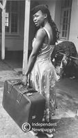 Woman stands with suitcase, Cape Town
