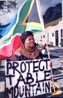 Woman holds flag and sign in protest, Cape Town