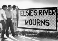 "Men look at the sign ""Elsies River Mourns"", Cape Town"