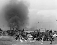 Convoy of army trucks with smoke in the background, Cape Town