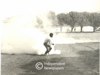 Man picks up a teargas canister that has been set off, Cape Town