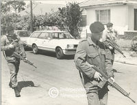 Marines walk down a street with rifles at the ready, Cape Town