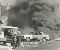 Policeman looks at a motor vehicle that has been set alight, Cape Town