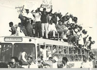 A bus so full, that people are sitting on the roof, Cape Town