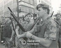 Members of the army stand relaxed talking to one another, Cape Town