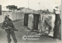A riot policeman stands near an overturned car that was set alight, Cape Town