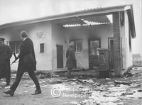 Policeman looks at the damage done to a building by rioters, Cape Town