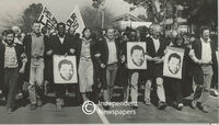 Protesters march holding placards of a young Nelson Mandela, Cape Town