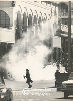 Silhouette of a woman fleeing from teargas, Cape Town