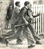Policeman runs holding a baseball bat and gun, Cape Town