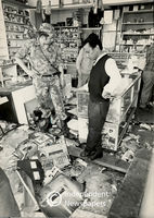 Policeman surveys the damage done to a shop, Cape Town