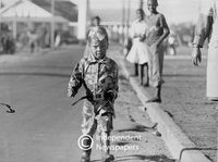Young boy pretends to be a riot policeman, Cape Town