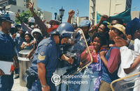 Policeman keeps students at bay outside the gates to Parliament, Cape Town