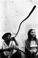 Man blowing a horn, sitting next to a woman