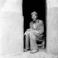 Xhosa man sitting in a doorway smoking a pipe, Transkei, South Africa