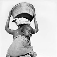 Xhosa woman with child on back, carrying water, Transkei, South Africa