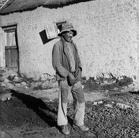 Man standing in a yard, Genadendal, South Africa