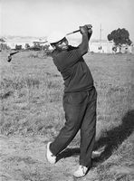 Man swinging golf club in an open field, Eastern Cape, South Africa