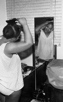 Woman brushing hair while looking in mirror, Eastern Cape, South Africa
