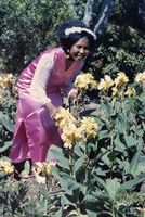 Bridesmaid in pink dress standing amongst yellow flowers, Eastern Cape, South Africa