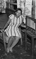 Woman sitting in a chair and listening to the radio, Eastern Cape, South Africa