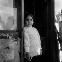 Young girl standing in a doorway of a shop in District Six, Cape Town, South Africa
