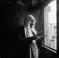 Woman reading a letter in the doorway, District Six, Cape Town, South Africa