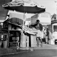 Woman pays a roadside vendor, District Six, Cape Town, South Africa